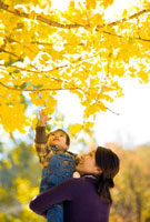 紅葉の下の男の子と母親