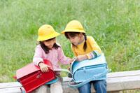 学校帰りに公園のベンチで本を見る女の子たち 22946001874| 写真素材・ストックフォト・画像・イラスト素材|アマナイメージズ