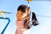 公園の遊具にぶら下がる女の子 22946001881| 写真素材・ストックフォト・画像・イラスト素材|アマナイメージズ