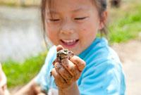 田んぼでカエルを見て笑う女の子