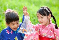 袋に入った金魚を見て笑う女の子たち 22946002013| 写真素材・ストックフォト・画像・イラスト素材|アマナイメージズ