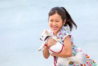 犬を抱いて浜辺を走る女の子