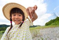 河原でトンボを持つ女の子 22946002104| 写真素材・ストックフォト・画像・イラスト素材|アマナイメージズ
