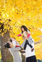 イチョウ並木で子供を抱き上げて遊ぶ家族 22946002297A| 写真素材・ストックフォト・画像・イラスト素材|アマナイメージズ