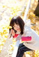 イチョウの葉を持って柵に登る女の子