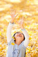 落ちてくるイチョウの葉で遊ぶ女の子 22946002304| 写真素材・ストックフォト・画像・イラスト素材|アマナイメージズ