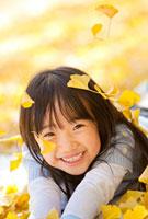 落ちてくるイチョウの葉で遊ぶ女の子 22946002307| 写真素材・ストックフォト・画像・イラスト素材|アマナイメージズ