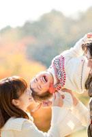 紅葉の公園で息子を肩車して遊ぶ親子