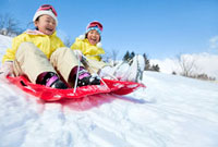 ソリで雪の斜面を滑る女の子達 22946002396| 写真素材・ストックフォト・画像・イラスト素材|アマナイメージズ