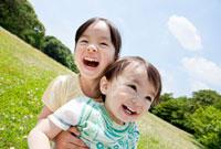 公園で笑う姉と弟
