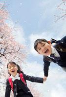 桜の下で手をつなぐ新一年生の男の子と女の子