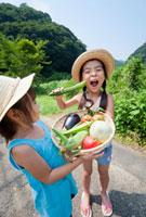収穫した野菜とキュウリをかじる女の子