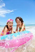 海で浮き輪に捕まって遊ぶ姉と弟