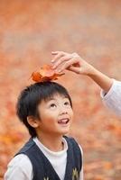 母親に落ち葉を頭に乗せてもらう男の子 22946002794| 写真素材・ストックフォト・画像・イラスト素材|アマナイメージズ