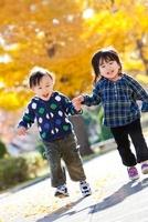 紅葉の公園で手をつないで走る男の子と女の子