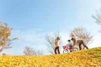 落ち葉の公園で遊ぶ4人家族