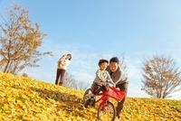 落ち葉の公園で自転車に乗って遊ぶ4人家族