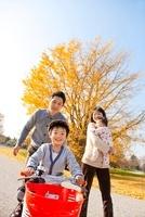 落ち葉の公園で自転車に乗って遊ぶ4人家族 22946002904| 写真素材・ストックフォト・画像・イラスト素材|アマナイメージズ