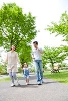 新緑の公園を走る3人家族