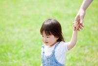 新緑の公園で母親と手をつなぐ女の子