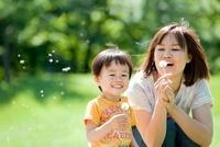公園で母親とタンポポの綿毛で遊ぶ男の子