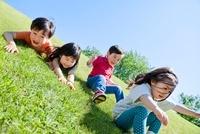 公園の斜面を滑って遊ぶ子供たち