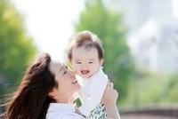 公園で息子を抱き上げる母親
