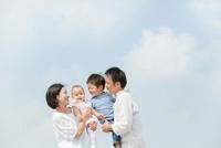 公園で両親に抱かれて笑う子供たち