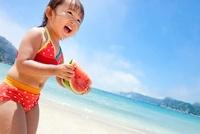 海辺でスイカを食べる女の子