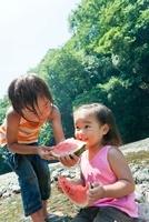 河原で妹にスイカを食べさせる兄