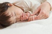 お昼寝をする娘の手に触れる母親の手