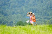 夏の土手でアミを持って遊ぶ姉と弟