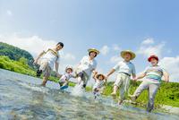 夏の河原で遊ぶ三世代家族