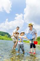 夏の河原で川遊びをする4人家族