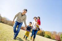 紅葉の公園を歩く4人家族