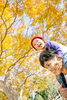 紅葉の公園を息子を肩車して歩く父親
