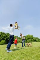 公園で遊ぶ4人家族と犬