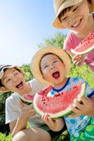 川原でスイカを食べる3人家族 22946004466| 写真素材・ストックフォト・画像・イラスト素材|アマナイメージズ