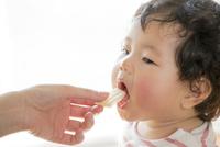 リビングで母親からお菓子をもらう娘 22946004531| 写真素材・ストックフォト・画像・イラスト素材|アマナイメージズ