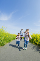 菜の花の咲く遊歩道を手をつないで走る4人家族