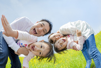 菜の花畑で娘たちを抱いて遊ぶ4人家族