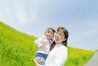 菜の花畑で母親に抱かれる娘