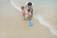 海辺で網を持つ父親と娘