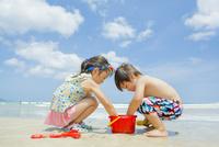 海辺で遊ぶ姉と弟