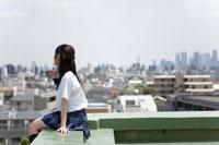 学校屋上から街を眺める女子高生