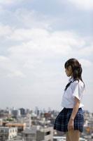 学校屋上に立って街を眺める女子高生