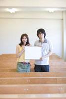教室でスケッチブックを持つ学生男女