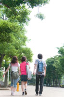 キャンパス内を歩く学生3人の後姿
