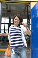 バスからおりる笑顔の女性