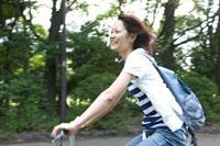 緑の中を自転車で走る若い女性